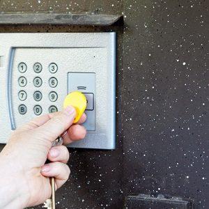 uma mão segurando uma chave do controle de acesso para condomínios