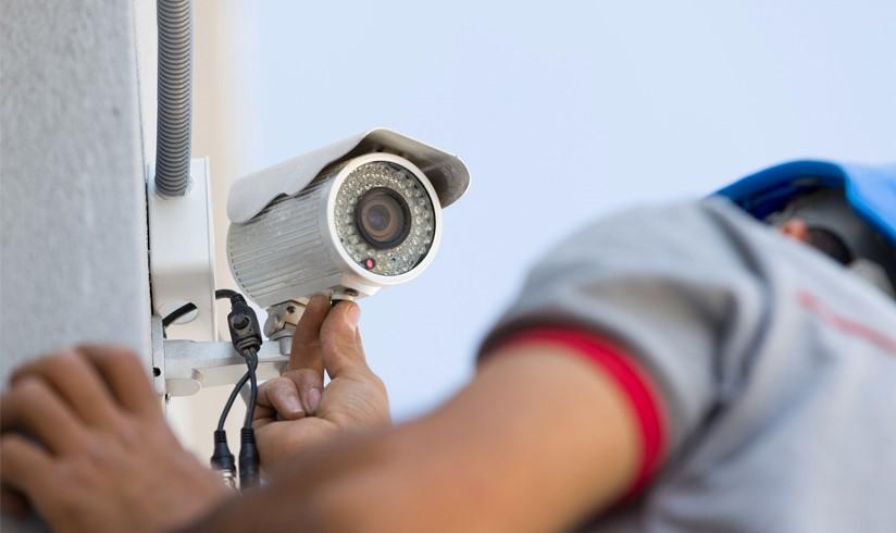 um técnico de segurança instalando uma câmera de Segurança residencial