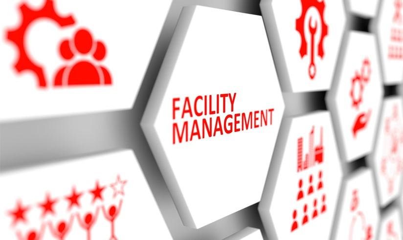 uma placa branca com letras vermelhas escrito Facilities Management