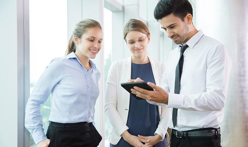 duas mulheres e um homem olhando para um tablet pesquisando sobre o mercado de facilities